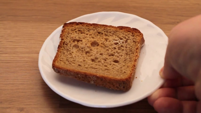 alapvető : Food. Slice of rye bread on a plate in a hand, kitchen wooden table background. Full HD 1920x1080 Stock mozgókép