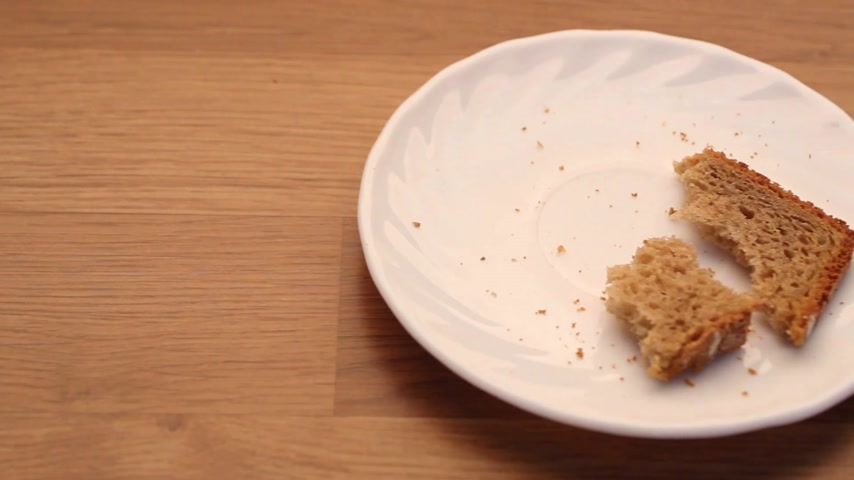 migalhas : Food. Slice of rye bread and crumbs on plate kitchen wooden table background. Full HD with motorized slider. Stock Footage