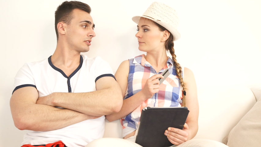 Young couple with tablet pc and credit card on sofa at home doing shopping on internet or planning holidays, having a serious conversation Стоковые видеозаписи