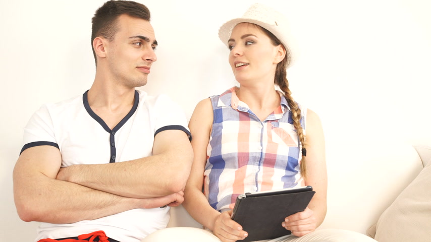 Young couple with tablet pc and credit card on sofa at home doing shopping on internet or planning holidays, having serious conversation strife.