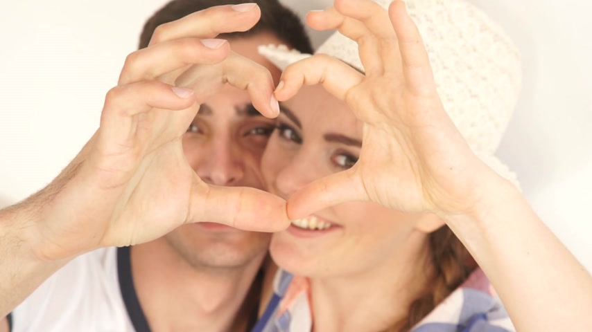 Love concept. Young couple and man forming heart shape with their fingers hands