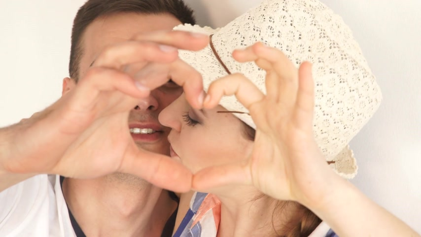Love concept. Young couple and man forming heart shape with their fingers and kissing