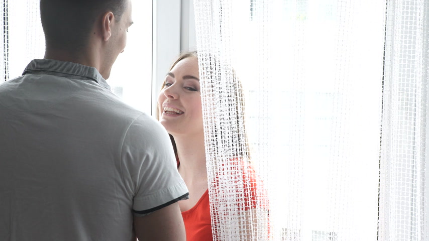 Couple flirting, young woman and man talking together at home