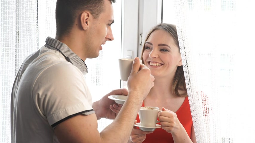 Attractive couple drinking coffee at home, man and woman holding cups with hot beverage at home