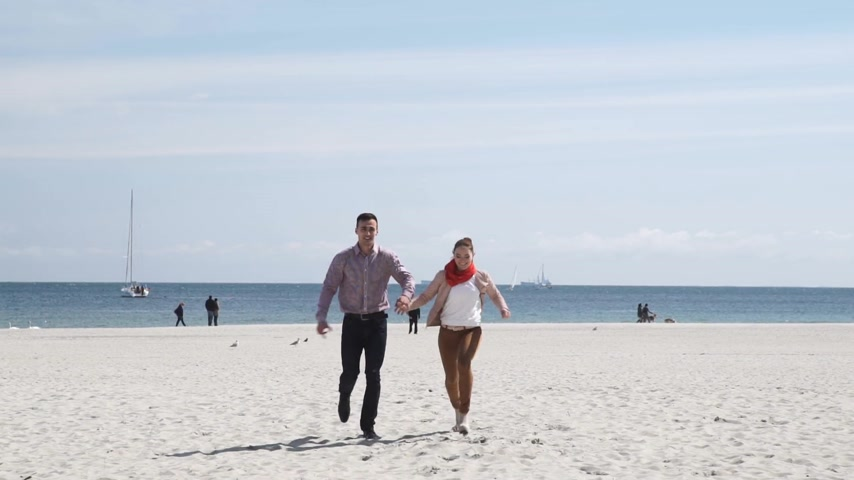 Happy young couple in love walking on sandy beach at sunny cold day.