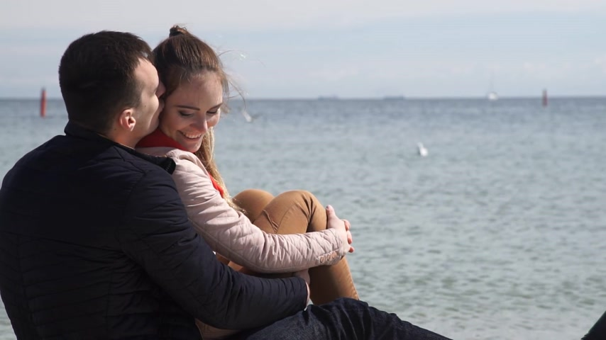 Loving couple spending time together, sitting on the beach, enjoying the beautiful sea landscape, side view Wideo