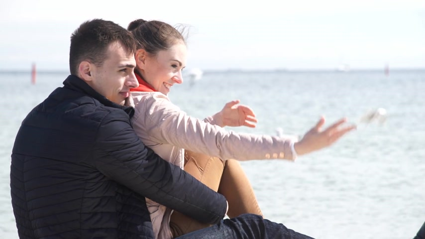 Loving couple spending time together, sitting on the beach, enjoying the beautiful sea landscape, side view Stock Footage