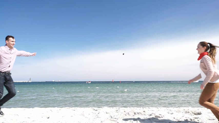 Happy young couple in love walking on sandy beach at sunny day. Woman and man enjoying love on date or honeymoon.