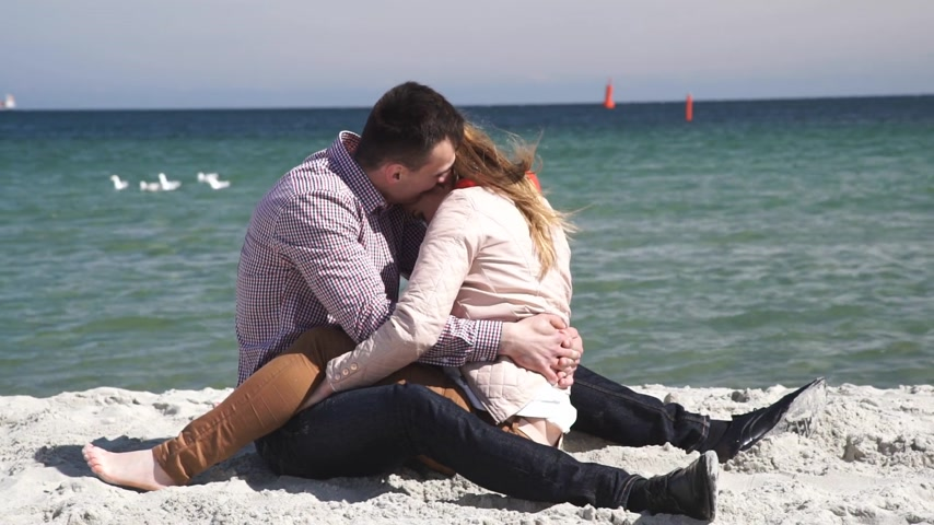 Loving couple spending time together, sitting on beach hugging having fun sunny cold day