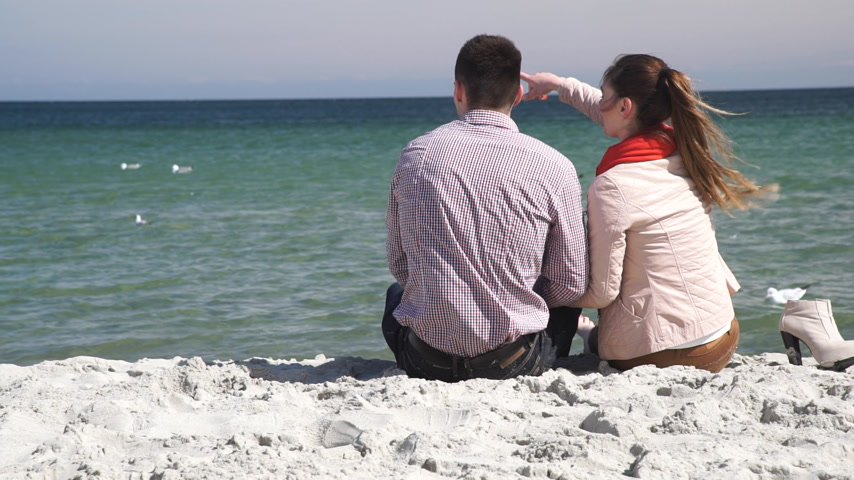 Loving couple spending time together, sitting on beach, enjoying beautiful sea landscape, rear view Wideo
