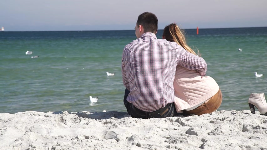 Loving couple spending time together, sitting on beach, enjoying beautiful sea landscape, rear view Стоковые видеозаписи