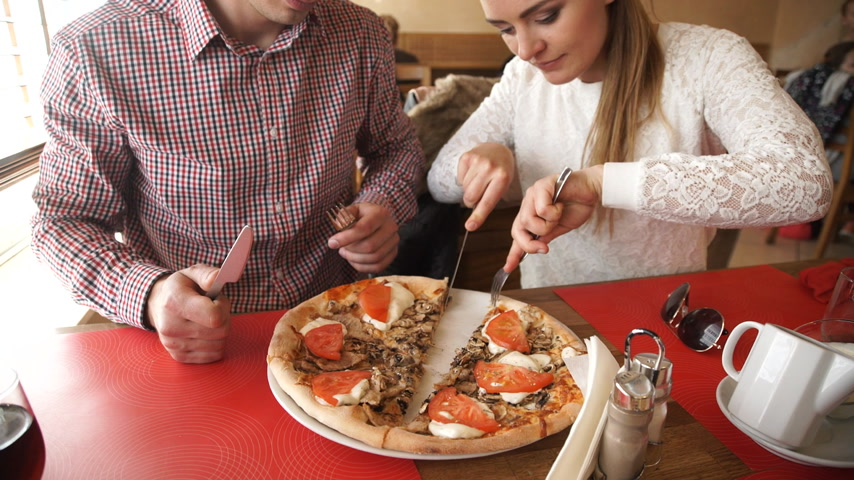 Young couple eating pizza in restaurant.