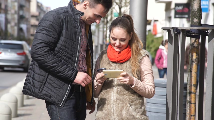 woman and man using mobile phone outside in street. Young urban couple hanging out in the city.