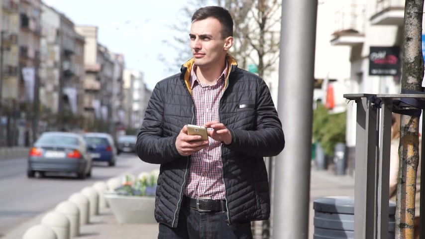 young man and woman bump into each other while texting and walking in city street