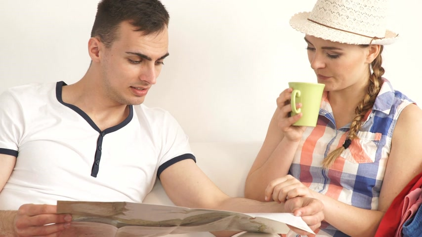 Young couple sitting on couch in living room looking at map, planning vacation trip. Стоковые видеозаписи