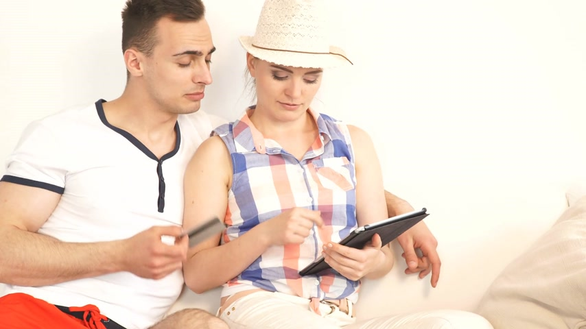 předpovídání : consumerism leisure and people concept. Young couple with tablet pc and credit card on sofa at home doing shopping on internet or planning vacation trip