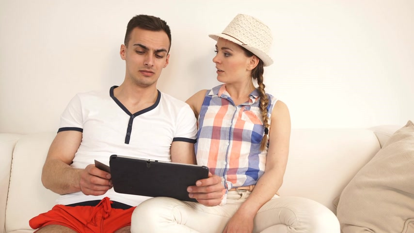 Young couple with tablet pc and credit card on sofa at home doing shopping on internet or planning holidays, having a serious conversation. Wideo