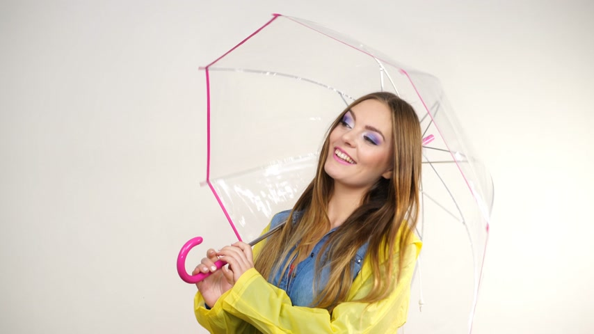 Woman fashionable rainy girl wearing waterproof yellow coat holding transparent umbrella studio shot 4K ProRes HQ codec Стоковые видеозаписи