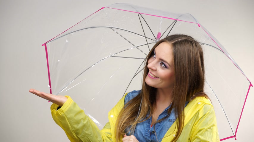 Woman rainy girl in waterproof yellow coat standing with transparent umbrella stretching arm, holds out her palm to catch rain falling water. Forecasting weather season concept 4K ProRes HQ codec