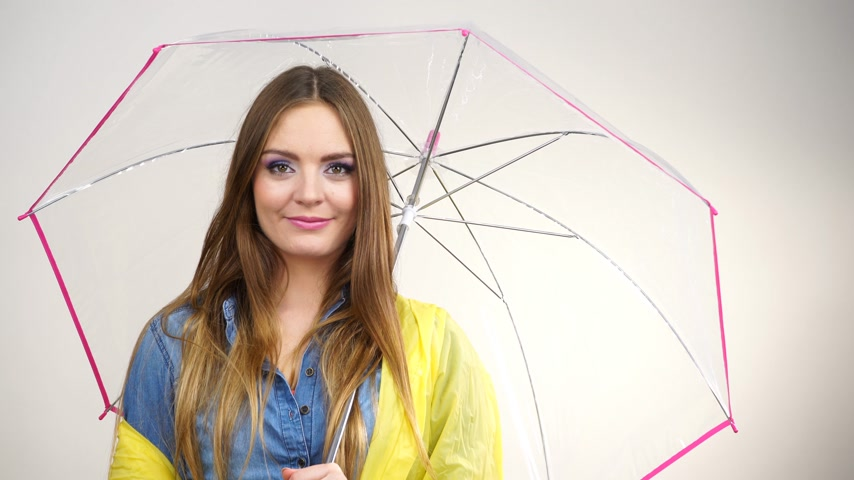Woman fashionable rainy girl wearing waterproof yellow coat holding transparent umbrella studio shot 4K ProRes HQ codec Stock Footage