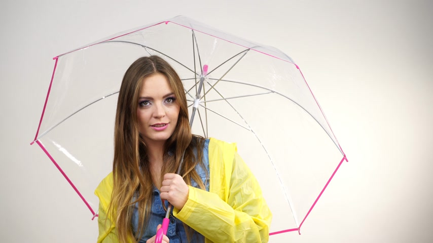 Woman fashionable rainy girl wearing rainproof yellow coat holding transparent umbrella studio shot. Meteorology, forecasting and weather season concept 4K ProRes HQ codec