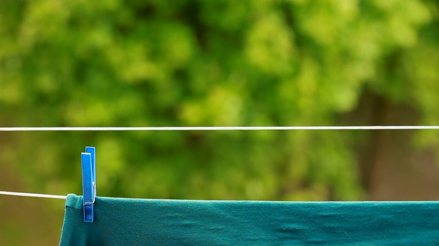 prendedor de roupa : Green clothes hanging to dry on a laundry line outdoor. Housework. Stock Footage