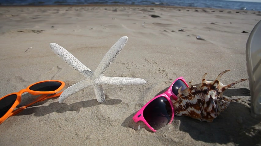 homokóra : Colorful sunglasses, flip flops and starfish seastar on the sandy beach. Summer vacation. Full HD with motorized slider. 1080p. Stock mozgókép