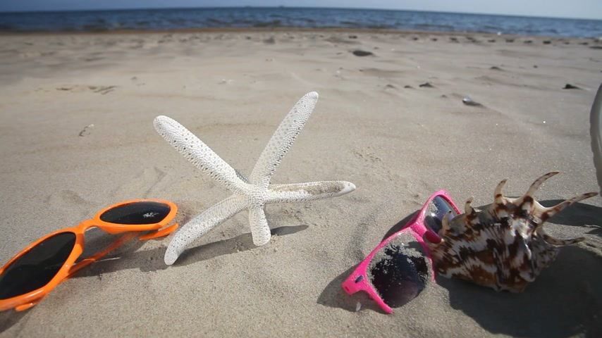 homokóra : Colorful sunglasses, seashells and starfish seastar on the sandy beach. Summer vacation. Full HD with motorized slider. 1080p.