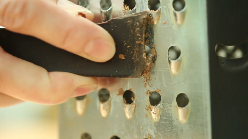 grated : Closeup human hand holding dark chocolate piece and making shavings curls using grater Stock Footage