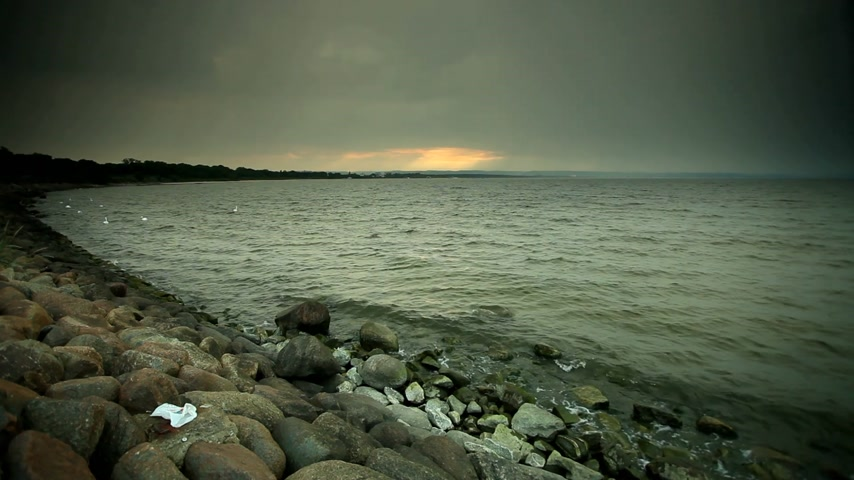 baltık denizi : Stone sea shore and waves by evening, dark sky after sunset. Nature landscape.