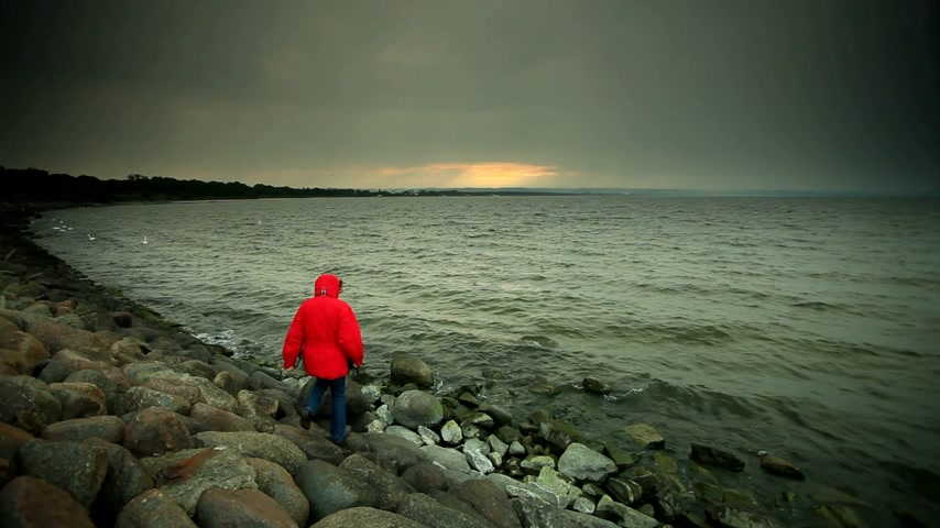 Mature woman wearing red jacket walking on stone sea shore in cold evening sky after sunset.