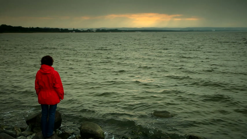 Mature woman wearing red jacket standing on stone sea shore in cold evening sky after sunset.