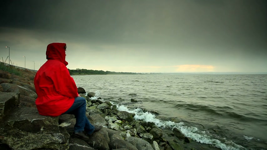 Mature woman wearing red jacket sitting on stone sea shore in cold evening sky after sunset.