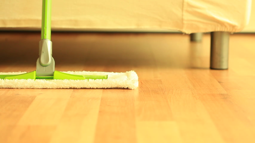 mopping : House cleaning, green mop standing on wooden floor. Dolly sliding shot. Full Hd 1920X1080P with motorized slider.