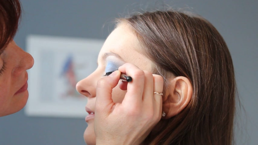 arcszín : Cosmetic beauty procedures and makeover concept. Closeup woman face eyes painting. Makeup artist applying black eye liner to model eye. Stock mozgókép