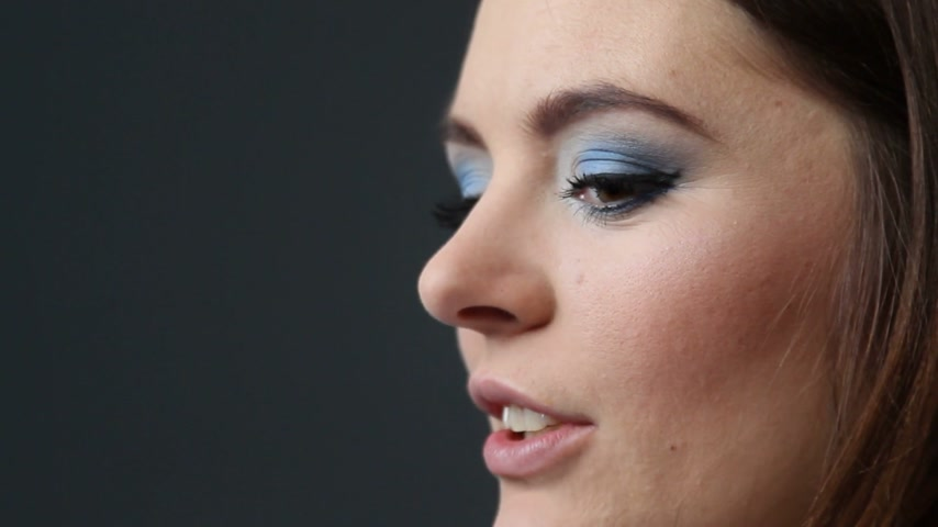 they : Woman face profile with blue eyes shadows makeup on gray background Stock Footage