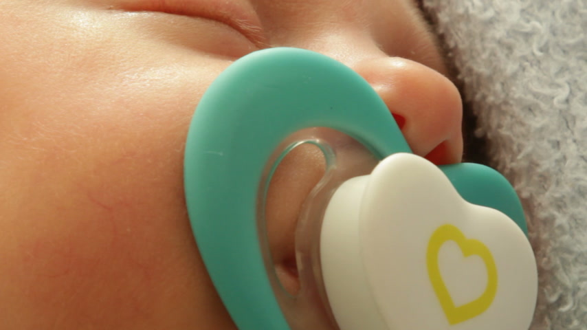 Closeup little newborn baby girl 24 days sleeping with dummy in mouth. Wideo