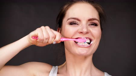 белить : Woman brushing cleaning teeth. Girl with toothbrush. Oral hygiene. Dark black background 4K ProRes HQ codec