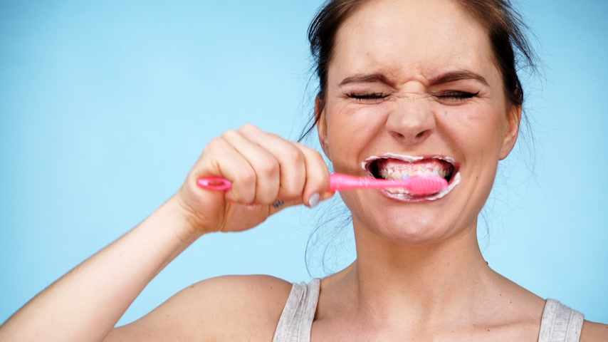 diário : Woman brushing cleaning teeth. Girl with toothbrush. Oral hygiene. Blue background 4K ProRes HQ codec