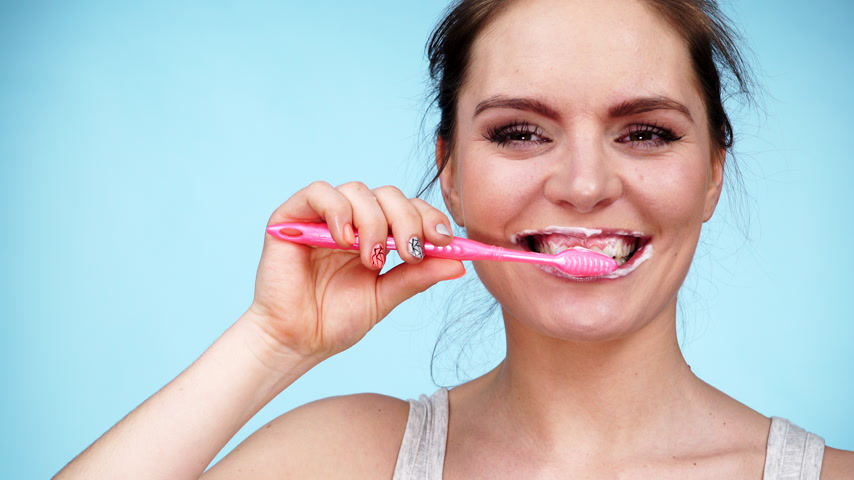 белить : Woman brushing cleaning teeth. Girl with toothbrush. Oral hygiene. Blue background 4K ProRes HQ codec