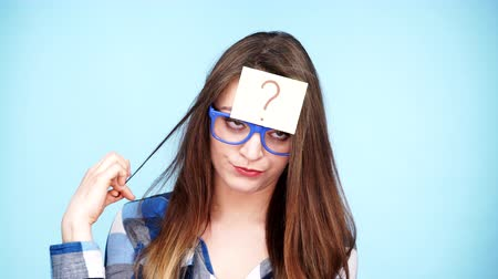 запомнить : Woman confused thinking seeks a solution, paper card with question mark on her head. Doubtful young female studio shot on blue background. 4K ProRes HQ codec Стоковые видеозаписи