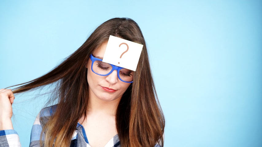 forget : Woman confused thinking seeks a solution, paper card with question mark on her head. Doubtful young female studio shot blue background. 4K ProRes HQ codec