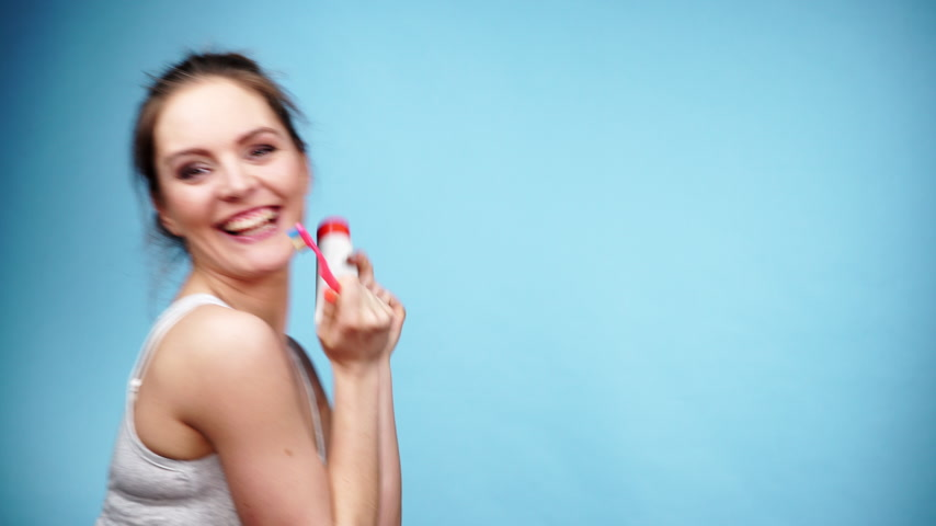 escovação : Woman holding brush and tooth paste for teeth cleaning. Happy funny smiling girl with toothbrush. Oral hygiene. Studio shot blue background 4K ProRes HQ codec