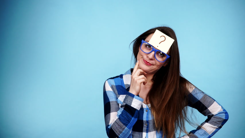 ponto de interrogação : Woman confused thinking seeks a solution, paper card with question mark on her head. Doubtful young female studio shot blue background. 4K ProRes HQ codec