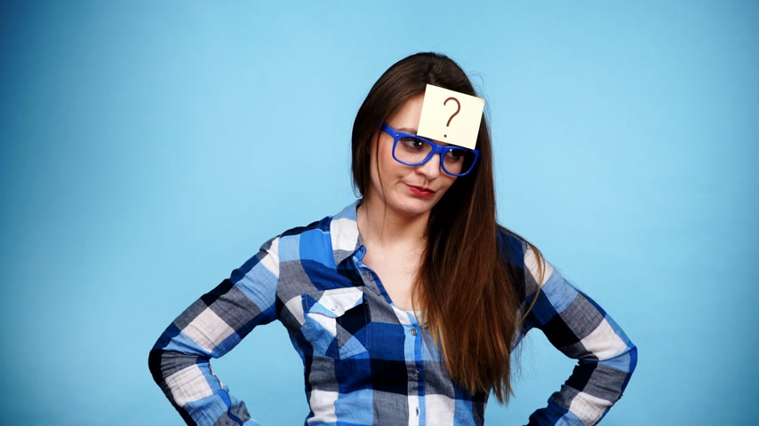 plano : Woman confused thinking seeks a solution, paper card with question mark on her head. Doubtful young female studio shot blue background. 4K ProRes HQ codec