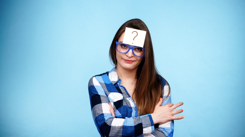 pensamento : Woman confused thinking seeks a solution, paper card with question mark on her head. Doubtful young female studio shot blue background. 4K ProRes HQ codec