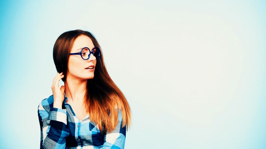 favori : Woman or student long hair girl wearing eyeglasses standing and smiling looking sideways. Casual young female with specs studio shot on blue, filtered footage 4K ProRes HQ codec.