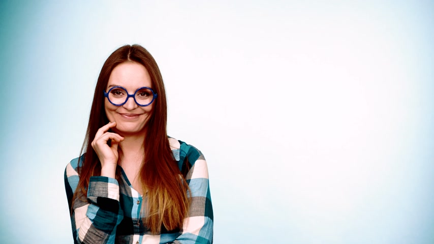 favori : Woman or student long hair girl wearing eyeglasses standing and smiling. Casual young female with specs studio shot on blue, filtered footage 4K ProRes HQ codec.