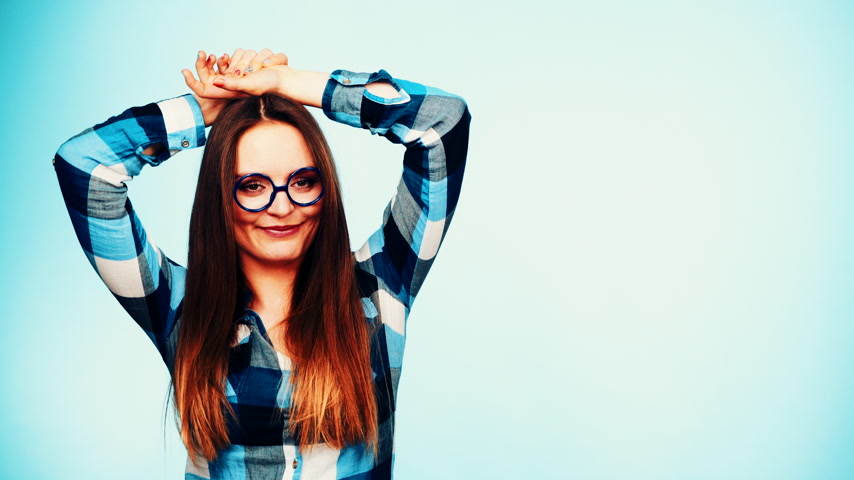 お気に入り : Woman or student long hair girl wearing eyeglasses standing and smiling. Casual young female with specs studio shot on blue, filtered footage 4K ProRes HQ codec.