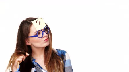 ponto de interrogação : Woman confused thinking seeks a solution, paper card with question mark on her head. Doubtful young female studio shot isolated on white background. 4K ProRes HQ codec Stock Footage